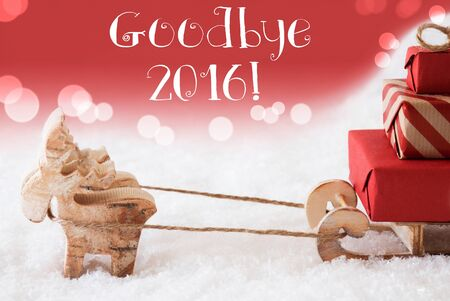 christmassy: Moose Is Drawing A Sled With Red Gifts Or Presents In Snow. Christmas Card For Seasons Greetings. Red Christmassy Background With Bokeh Effect. English Text Goodbye 2016 For Happy New Year