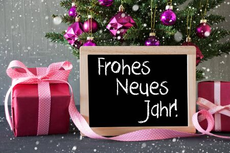 jahr: Chalkboard With German Text Frohes Neues Jahr Means Happy New Year. Christmas Tree With Rose Quartz Balls, Snowflakes. Gifts Or Presents In The Front Of Cement Background. Stock Photo