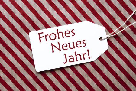 jahr: One Label On A Red And Brown Striped Wrapping Paper. Textured Background. Tag With Ribbon. German Text Frohes Neues Jahr Means Happy New Year