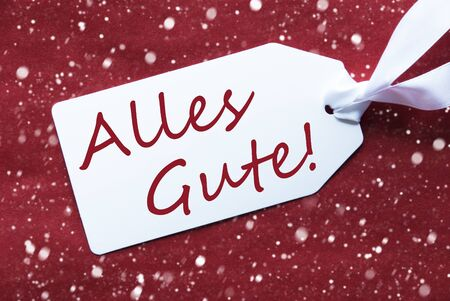 best wishes: One White Label On A Red Textured Background. Tag With Ribbon And Snowflakes. German Text Alles Gute Means Best Wishes