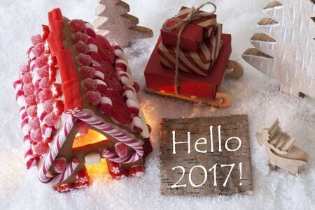 Label With English Text Hello 2017 For Happy New Year. Gingerbread House On Snow With Christmas Decoration Like Trees And Moose. Sleigh With Christmas Gifts Or Presents.