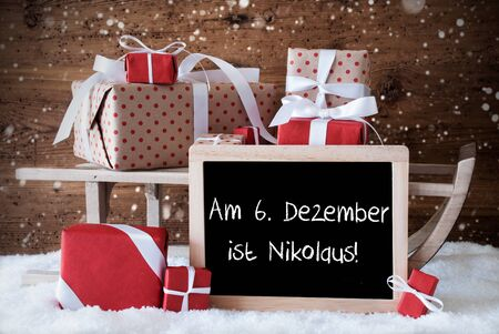 nikolaus: Chalkboard With German Text Am 6. Dezember Ist Nikolaus Means December 6th Is Nicholas Day. Sled With Christmas And Winter Decoration And Snowflakes. Gifts And Presents On Snow With Wooden Background. Stock Photo