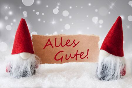 gnomos: Christmas Greeting Card With Two Red Gnomes. Sparkling Bokeh And Noble Silver Background With Snow. German Text Alles Gute Means Best Wishes