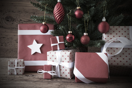 nostalgic: Nostalgic Christmas Tree With Gifts Or Presents In The Front Of Wooden Background. White Ribbon With Bow. Rustic Or Retro Style. Christmas Decoration Like Balls