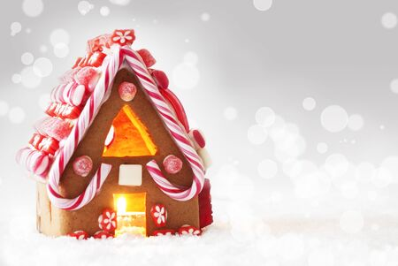 atmosphere: Gingerbread House In Snowy Scenery As Christmas Decoration. Candlelight For Romantic Atmosphere. Silver Background With Bokeh Effect. Copy Space For Advertisement
