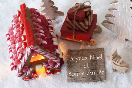 bonne: Label With French Text Joyeux Noel Et Bonne Annee Means Merry Christmas And Happy New Year. Gingerbread House On Snow With Christmas Decoration Like Trees And Moose. Sleigh With Christmas Gifts.
