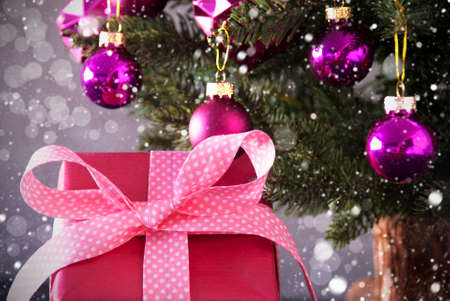 rose quartz: One Gift Or Present In The Front Of Cement Background. Christmas Tree With Rose Quartz Balls, Snowflakes And Bokeh Effect.