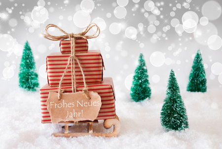 jahr: Sleigh Or Sled With Christmas Gifts Or Presents. Snowy Scenery With Snow And Trees. White Sparkling Background With Bokeh Effect. Label With German Text Frohes Neues Jahr Means Happy New Year