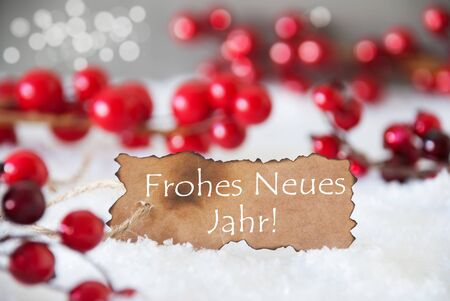 Burnt Label With German Text Frohes Neues Jahr Means Happy New Year. Red Christmas Decoration On Snow. Cement Wall As Background With Bokeh Effect. Card For Seasons Greetings