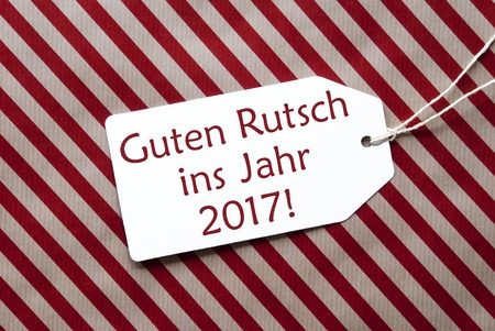 guten tag: One Label On A Red And Brown Striped Wrapping Paper. Textured Background. Tag With Ribbon. German Text Guten Rutsch Ins Jahr 2017 Means Happy New Year Stock Photo