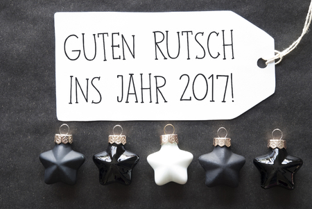 ins: Label With German Text Guten Rutsch Ins Jahr 2017 Means Happy New Year 2017. Black And White Christmas Tree Balls On Black Paper Background. Christmas Decoration Or Texture. Flat Lay View