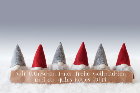 Label With German Text Wir Wuenschen Frohe Weihnachten Und Ein Gutes Neues Jahr Means Merry Christmas And Happy New Year. Christmas Greeting Card With Gnomes. Silver Background With Snow.