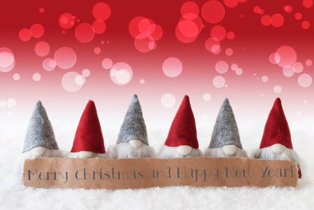 christmassy: Label With English Text Merry Christmas And Happy New Year. Christmas Greeting Card With Red Gnomes. Bokeh And Christmassy Background With Snow. Stock Photo