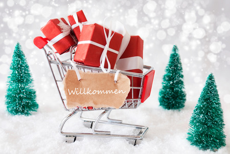 willkommen: Trollye With Christmas Presents Or Gifts. Snowy Scenery With Snow And Trees. Sparkling Bokeh Effect. Label With German Text Willkommen Means Welcome