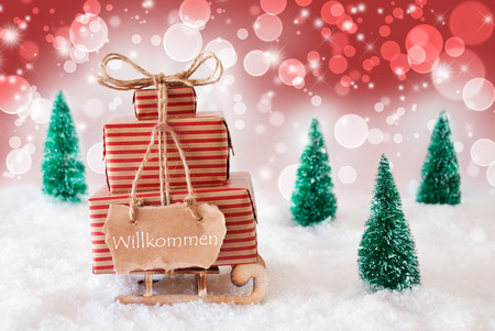 willkommen: Sleigh Or Sled With Christmas Gifts Or Presents. Snowy Scenery With Snow And Trees. Red Sparkling Background With Bokeh Effect. Label With German Text Willkommen Means Welcome