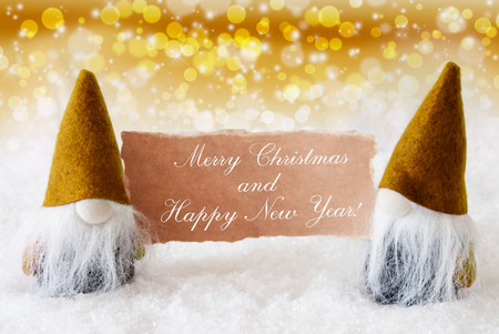 gnomos: Christmas Greeting Card With Two Golden Gnomes. Sparkling Bokeh And Noble Background With Snow. English Text Merry Christmas And Happy New Year Foto de archivo