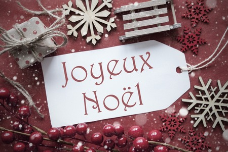 joyeux: Nostalgic Christmas Decoration Like Gift Or Present, Sleigh. Card For Seasons Greetings With Red Paper Background. French Text Joyeux Noel Means Merry Christmas