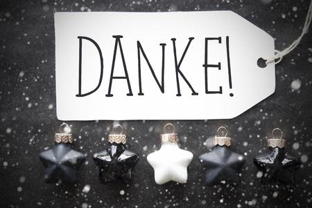 you black: Etiqueta con el texto alemán Medios Danke le agradece. Negro y blanco Navidad bolas del árbol En El Papel Negro Fondo con los copos. Textura de Navidad o la decoración. Lay plana Vista