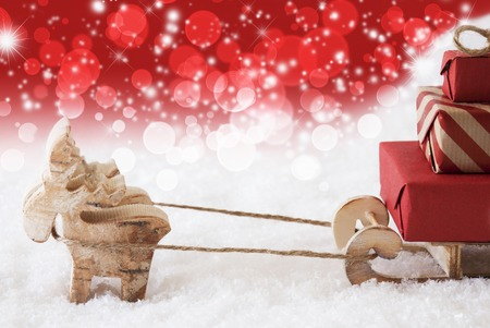christmassy: Moose Is Drawing A Sled With Red Gifts Or Presents In Snow. Christmas Card For Seasons Greetings. Copy Space For Advertisement. Red Christmassy Background With Bokeh Effect. Stock Photo