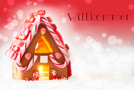 willkommen: Gingerbread House In Snowy Scenery As Christmas Decoration. Candlelight For Romantic Atmosphere. Red Background With Bokeh Effect. German Text Willkommen Means Welcome