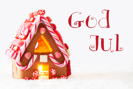 house of god: Gingerbread House In Snowy Scenery As Christmas Decoration With White Background. Candlelight For Romantic Atmosphere. Swedish Text God Jul Means Merry Christmas