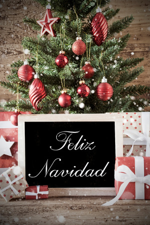 nostalgic christmas: Nostalgic Christmas Card For Seasons Greetings. Christmas Tree With Balls. Gifts Or Presents In The Front Of Wooden Background. Chalkboard With Spanish Text Feliz Navidad Means Merry Christmas