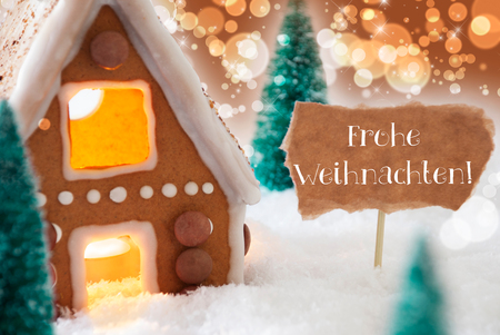 weihnachten: Gingerbread House In Snowy Scenery As Christmas Decoration. Christmas Trees And Candlelight. Bronze And Orange Background With Bokeh Effect. German Text Frohe Weihnachten Means Merry Christmas Stock Photo
