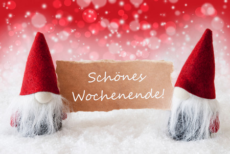 wochenende: Christmas Greeting Card With Two Red Gnomes. Sparkling Bokeh And Christmassy Background With Snow. German Text Schoenes Wochenende Means Happy Weekend