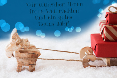 German Text Frohe Weihnachten Und Gutes Neues Jahr Means Merry Christmas And Happy New Year. Moose Is Drawing A Sled With Red Gifts Or Presents In Snow. Blue Background With Bokeh Effect. Stock Photo