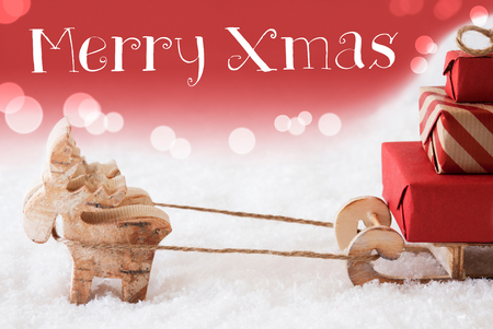 christmassy: Moose Is Drawing A Sled With Red Gifts Or Presents In Snow. Christmas Card For Seasons Greetings. Red Christmassy Background With Bokeh Effect. English Text Merry Xmas Stock Photo