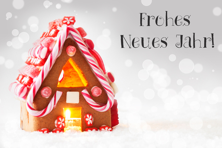 jahr: Gingerbread House In Snowy Scenery As Christmas Decoration. Candlelight For Romantic Atmosphere. Silver Background With Bokeh Effect. German Text Frohes Neues Jahr Means Happy New Year
