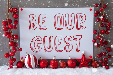 like english: Label With English Text Be Our Guest. Red Christmas Decoration Like Balls On Snow. Urban And Modern Cement Wall As Background With Snowflakes.