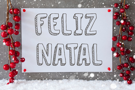 natal: Label With Portuguese Text Feliz Natal Means Merry Christmas. Red Christmas Decoration On Snow. Urban And Modern Cement Wall As Background With Snowflakes. Stock Photo