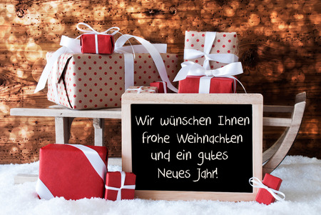 jahr: Chalkboard With German Text Frohe Weihnachten Und Ein Gutes Neues Jahr Means Merry Christmas And Happy New Year. Sled With Winter Decoration. Presents On Snow With Wooden Background And Bokeh Effect.