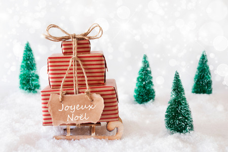 Sled With Christmas Gifts Or Presents. Snowy Scenery With Snow And Trees. White Sparkling Background With Bokeh Effect. Label With French Text Joyeux Noel Means Merry Christmas