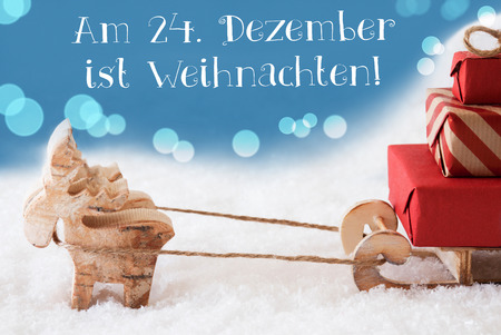 Moose Is Drawing A Sled With Red Gifts Or Presents In Snow. Christmas Card For Seasons Greetings. Light Blue Background With Bokeh Effect. German Text Am 24. Dezember Ist Weihnachten Means Christmas Stock Photo