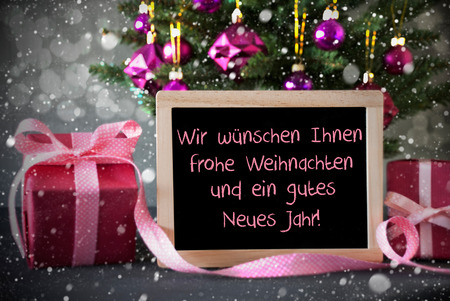 jahr: Chalkboard With German Text Frohe Weihnachten Und Ein Gutes Neues Jahr Means Merry Christmas And Happy New Year. Tree With Rose Quartz Balls, Snowflakes And Bokeh. Gifts With Cement Background. Stock Photo
