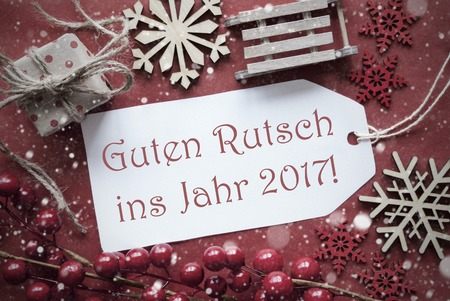 ins: Nostalgic Christmas Decoration Like Gift Or Present, Sleigh. Card For Seasons Greetings With Red Paper Background. German Text Guten Rutsch Ins Jahr 2017 Means Happy New Year Stock Photo