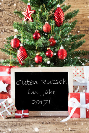 ins: Colorful Christmas With Tree With Balls And Snowflakes. Gifts Or Presents In The Front Of Wooden Background. Chalkboard With German Text Guten Rutsch Ins Jahr 2017 Means New Year 2017