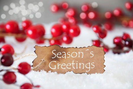 greetings card: Burnt Label With English Text Seasons Greetings. Red Christmas Decoration On Snow. Cement Wall As Background With Bokeh Effect. Card For Seasons Greetings