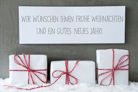 jahr: Label With German Text Frohe Weihnachten Und Ein Gutes Neues Jahr Means Merry Christmas And Happy New Year. Three Christmas Gifts Or Presents On Snow. Cement Wall As Background. Modern And Urban Style Stock Photo
