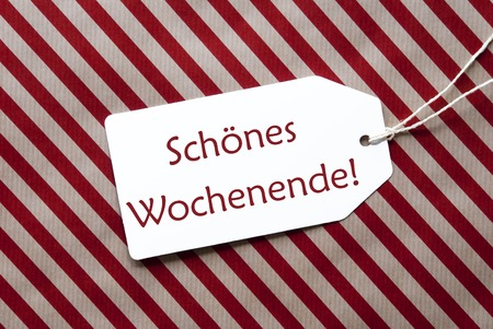wochenende: One Label On A Red And Brown Striped Wrapping Paper. Textured Background. Tag With Ribbon. German Text Schoenes Wochenende Means Happy Weekend