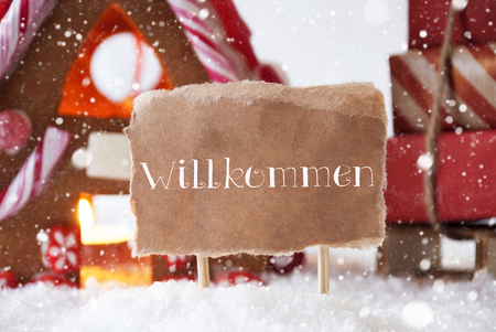 welcom: Gingerbread House In Snowy Scenery As Christmas Decoration. Sleigh With Christmas Gifts Or Presents And Snowflakes. Label With German Text Willkommen Means Welcom