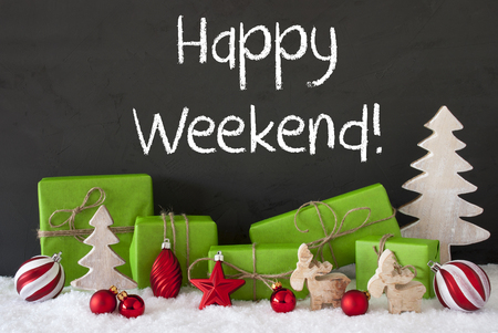 like english: English Text Happy Weekend. Green Gifts Or Presents With Christmas Decoration Like Tree, Moose Or Red Christmas Tree Ball. Black Cement Wall As Background With Snow. Stock Photo