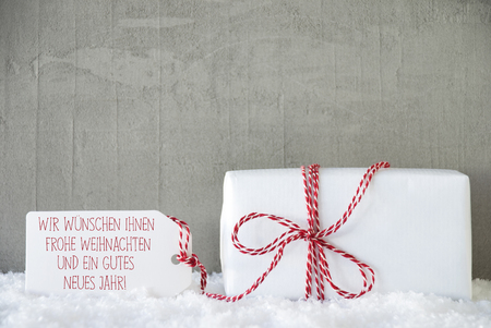 jahr: Label With German Text Wir Wuenschen Ihnen Frohe Weihnachten Und Ein Gutes Neues Jahr Means Merry Christmas And Happy New Year. One Present On Snow. Cement Or Concrete Wall As Background.