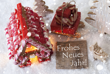 jahr: Label With German Text Frohes Neues Jahr Means Happy New Year. Gingerbread House On Snow With Christmas Decoration Like Trees And Moose. Sleigh With Christmas Gifts Or Presents And Snowflakes.