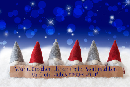 jahr: Label With German Text Wir Wuenschen Frohe Weihnachten Und Ein Gutes Neues Jahr Means Merry Christmas And Happy New Year. Card With Gnomes. Sparkling Bokeh And Blue Background With Snow And Stars.