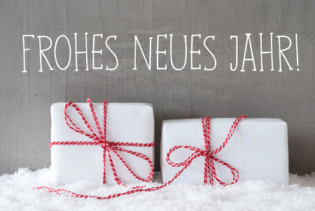 jahr: German Text Frohes Neues Jahr Means Happy New Year. Two White Christmas Gifts Or Presents On Snow. Cement Wall As Background. Modern And Urban Style.