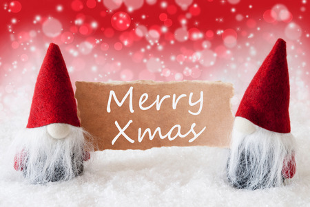 christmassy: Christmas Greeting Card With Two Red Gnomes. Sparkling Bokeh And Christmassy Background With Snow. English Text Merry Xmas