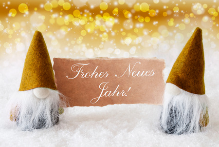 jahr: Christmas Greeting Card With Two Golden Gnomes. Sparkling Bokeh And Noble Background With Snow. German Text Frohes Neues Jahr Means Happy New Year